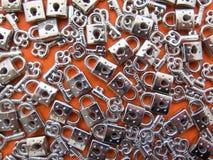 Lotti di poca serratura-e-chiave su fondo arancio fotografie stock