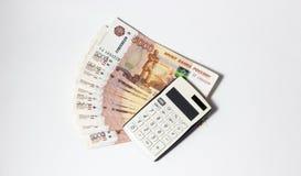 Lotti di soldi e di un calcolatore del primo piano fotografia stock