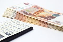 Lotti di soldi e di un calcolatore del primo piano immagini stock