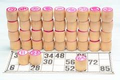 Lotto или bingo настольной игры Стена от деревянных бочонков lotto с номерами и карта на белом столе во время игры Винтажная игра стоковое фото rf