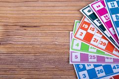 Lotto or Bingo Game Papers. Colorful lotto or bingo game papers with numbers and plastic lotto barrels, on wooden background Stock Image