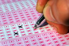 Lotto. Close-up of hand choosing lotto numbers Royalty Free Stock Image