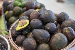 Lotto degli avocado maturi sulla ciotola ed uno della fetta di avocado da mostrare dentro di frutta fresca fotografia stock