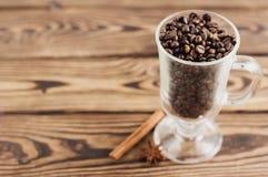 Lotto dei chicchi di caffè fritti in vetro trasparente per vin brulé con la maniglia e la gamba vicino ad un bastone di cannella  immagini stock