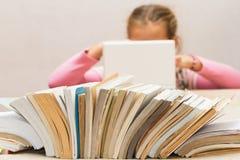 Lotto dei libri e di una ragazza con un computer portatile Immagine Stock Libera da Diritti