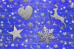 Lotto della stella del ferro, del cuore, di caro e fiocco di neve sul bordo di legno blu stagionato Fotografia Stock Libera da Diritti