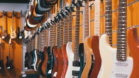 Lotto delle chitarre elettriche che appendono in un deposito di musica Strumenti musicali del negozio video d archivio