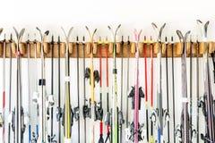 Lotto dello sci appeso sul supporto di legno su misura della parete al garage per stoccaggio stagionale Attrezzatura di sport inv fotografie stock libere da diritti