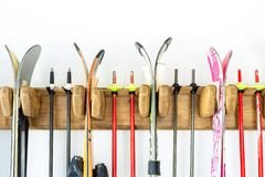 Lotto dello sci appeso sul supporto di legno su misura della parete al garage per stoccaggio stagionale Attrezzatura di sport inv fotografia stock libera da diritti