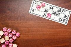 Lotto eller bingo för brädelek Trälottotrummor med nummer och kort på det bruna skrivbordet under en lek Tappninglek arkivbild