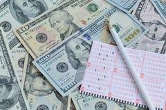 Lottoschein und Bleistift auf Dollarhintergrund Stockbild