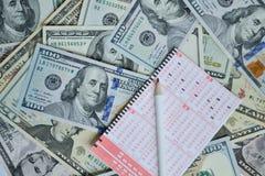 Lottoschein und Bleistift auf Dollarhintergrund Stockfotos