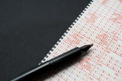 Lottsedel med pennan, personmarkeringsnummer Svart bakgrund, utrymme f?r text royaltyfri bild