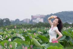 lotu领域的一名俏丽的妇女 免版税库存图片