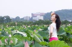 lotu领域的一名俏丽的妇女 免版税图库摄影