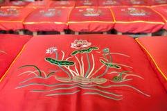 Lotus blommamodell på en röd bönkudde på en kinesisk tempel Royaltyfri Bild