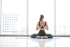 lotus Jeune beau yoga posant sur les fenêtres panoramiques sur le fond de ville Photographie stock