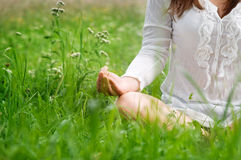 Lotus pose. Young woman meditating on meadow Royalty Free Stock Photos