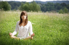 Lotus pose. Young woman meditating on meadow Stock Photos