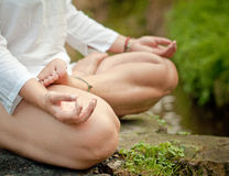 Lotus position. Young girl siting in lotus position near a stream Royalty Free Stock Images