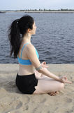 Lotus profile. Woman sitting in lotus position on a river bank, profile view, eyes closed Royalty Free Stock Photos