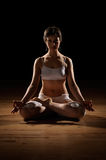 Lotus yoga position. A young woman in the lotus position during a yoga session Royalty Free Stock Photography