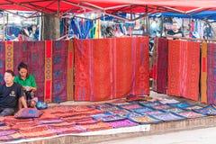 LOUANGPHABANG,老挝- 2017年1月11日:当地居民卖全国织品和纪念品在地方市场上 复制te的空间 库存照片