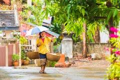 LOUANGPHABANG,老挝- 2017年1月11日:有篮子的妇女,步行沿着向下街道 复制文本的空间 免版税库存照片