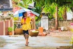 LOUANGPHABANG,老挝- 2017年1月11日:有篮子的妇女,步行沿着向下街道 复制文本的空间 库存照片