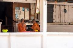 LOUANGPHABANG, ЛАОС - 11-ОЕ ЯНВАРЯ 2017: 2 буддийских монаха на крылечке здания Скопируйте космос для текста Стоковая Фотография RF