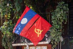 LOUANGPHABANG, LAOS - 11 DE ENERO DE 2017: Banderas en la fachada de un edificio Primer Foto de archivo