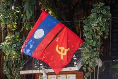 LOUANGPHABANG, LAOS - 11 DE JANEIRO DE 2017: Bandeiras na fachada de uma construção Close-up Foto de Stock