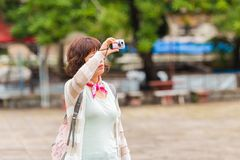LOUANGPHABANG, LAOS - 11 DE JANEIRO DE 2017: Turista da mulher que toma imagens dos arredores Copie o espaço para o texto Fotos de Stock Royalty Free