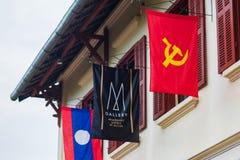 LOUANGPHABANG, LAOS - 11. JANUAR 2017: Flaggen auf der Fassade eines Gebäudes Nahaufnahme Lizenzfreies Stockfoto