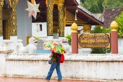 LOUANGPHABANG, LAOS - 11. JANUAR 2017: Frau mit Regenschirm auf dem Hintergrund des Tempels Kopieren Sie Raum für Text Stockbild
