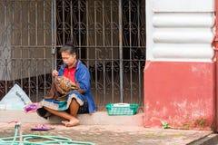 LOUANGPHABANG, LAOS - 11. JANUAR 2017: Frau näht auf einer Stadtstraße Kopieren Sie Raum für Text Stockfotografie