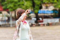 LOUANGPHABANG, LAOS - 11. JANUAR 2017: Frauentourist, der Fotos der Umgebungen macht Kopieren Sie Raum für Text Lizenzfreie Stockfotos