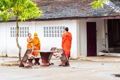 LOUANGPHABANG, LAOS - 11. JANUAR 2017: Mönche im Hof des Tempels Kopieren Sie Raum für Text Lizenzfreie Stockfotos