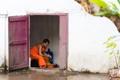LOUANGPHABANG LAOS - JANUARI 11, 2017: Munken arbetar i borggården av templet Kopiera utrymme för text Fotografering för Bildbyråer