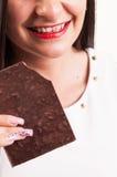 Louco para o chocolate, jovem mulher com o dente manchado do chocola Foto de Stock