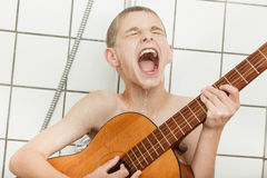 Loud child singing and playing guitar in shower royalty free stock photography