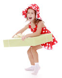Loud laughing little girl holds up a great gift Royalty Free Stock Image