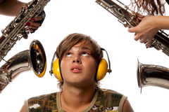 Loud noise. The young man in ear-phones and two saxophones. Loud noise stock image