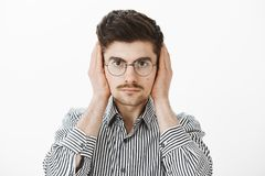 Loud roommate distract guy from freelance job. Portrait of bothered annoyed ordinary european male coworker in trendy. Glasses and striped shirt, covering ears stock photography