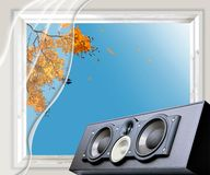 Loud speaker in front of a breezy morning window. Loud speaker in front of a wooden window where bright yellow autumn leaves over-hanging in the breeze of royalty free stock photo