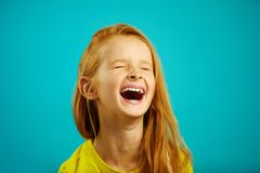 Loud and strong laughter of little girl with red hair, wearing yellow t-shirt, a shot of child on isolated blue. Loud and strong laughter of little girl with stock image