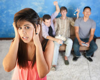 Loud Teens. Hispanic teen covers her ears to avoid the loud young men Royalty Free Stock Photography