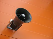 Loudspeaker. Black loudspeaker and orange wall royalty free stock photography