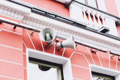 Loudspeaker mounted on an old building. On the street royalty free stock images