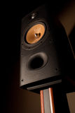 Loudspeaker on rosewood stand. A high-end stereo speaker in yellow, silver and black, mounted on rose wood stand. Interesting textures are visible on the cone of Royalty Free Stock Photos